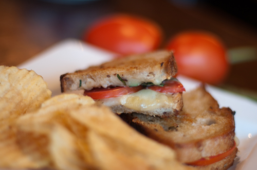 grilled cheese sandwich on plate with tomato and basil