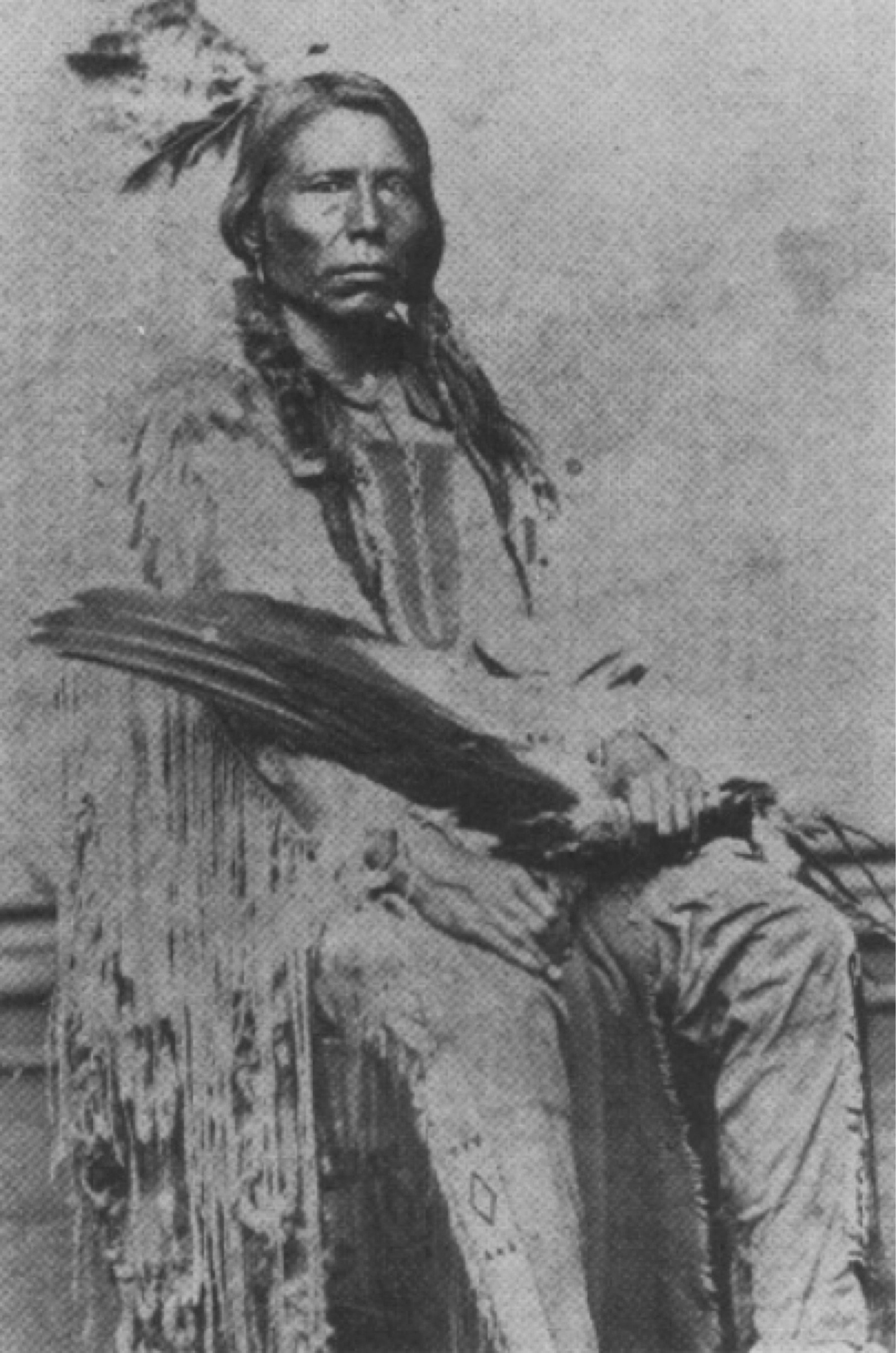 the man named Crazy Horse, sitting, he has long hair, and is wearing traditional dress.